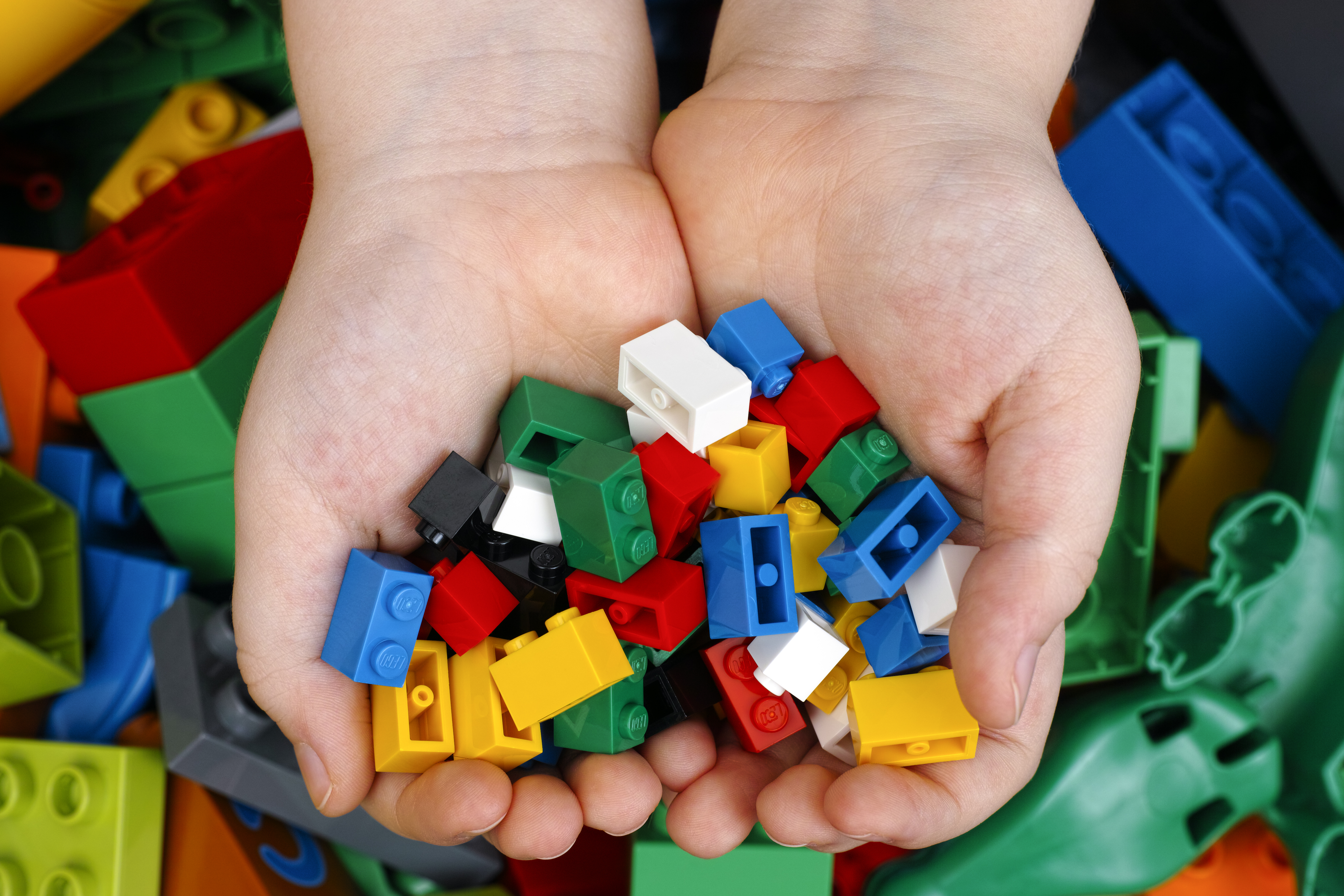 Image of hands holding LEGOs.