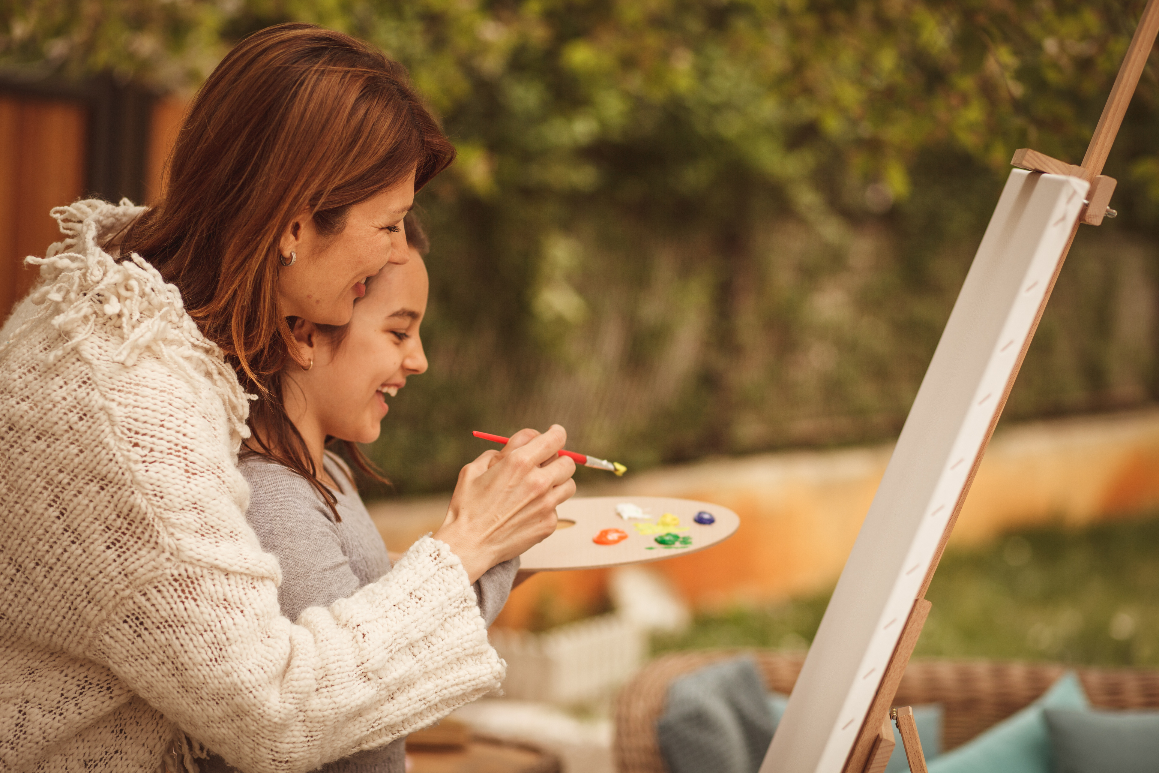 Image of a mother painting a canvas with her daughter.