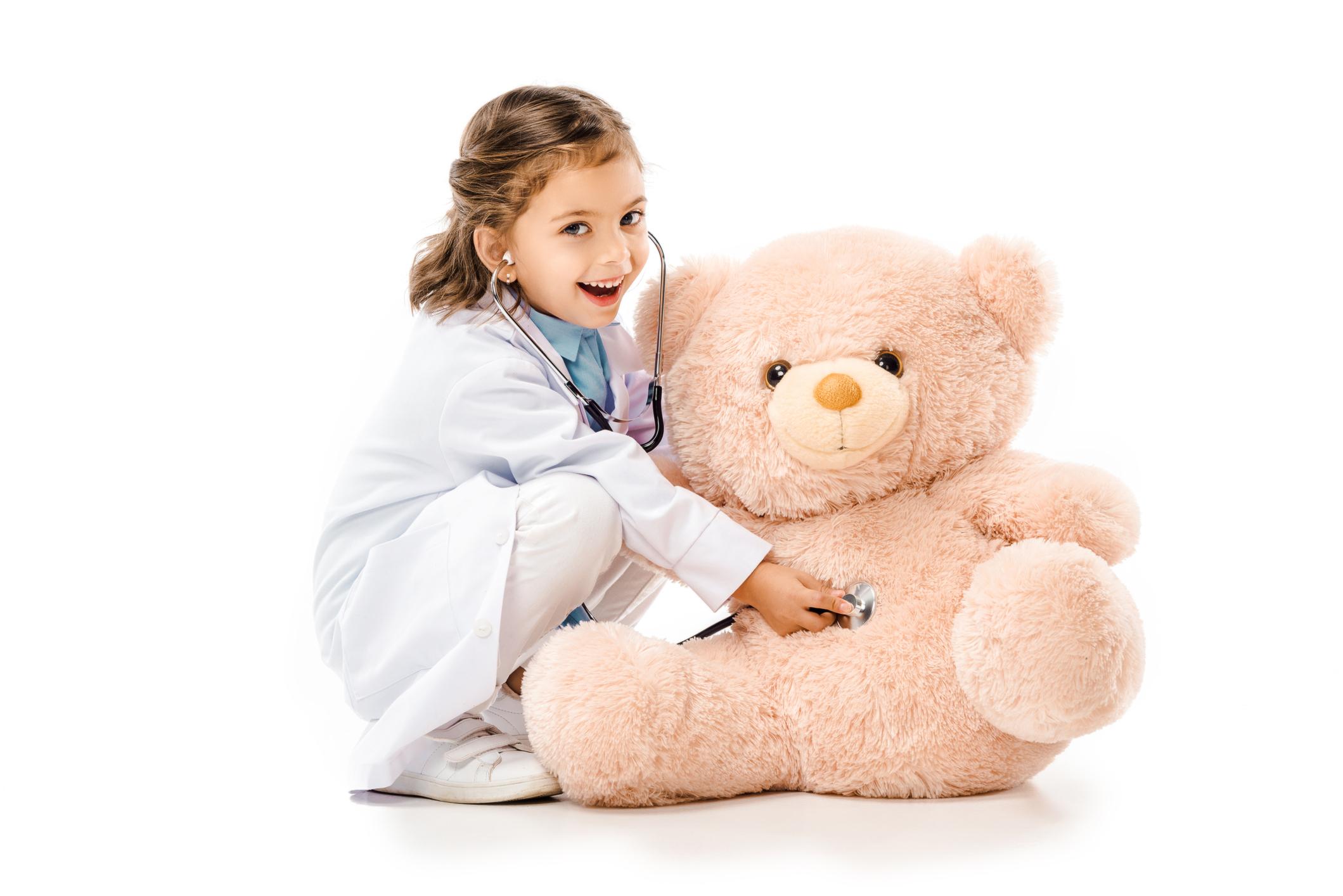 Kid listening to a stuffed teddy bear's heart.