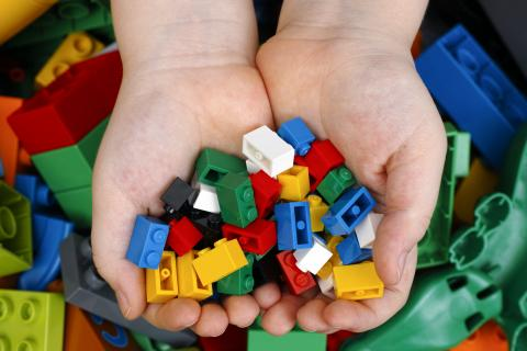 Photo of a child's hands full of LEGOs.